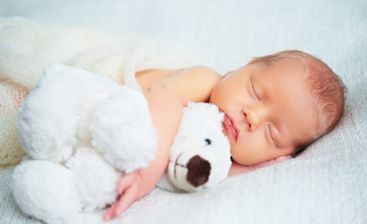 Cute newborn baby sleeps with a toy teddy bear white